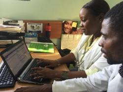 Dr. Regine Juste (left)  works on iSanté with Dr. Marinho Elisma, I-TECH Haiti's Lead Clinical Mentor.
