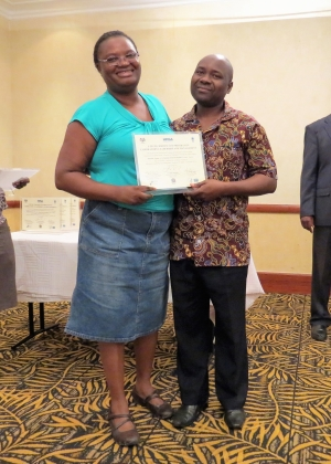 Mentor Dailes Nsofwa from CDC Zambia presents a certificate of completion to Kenneth Ngoma from Kasama General Hospital Laboratory.