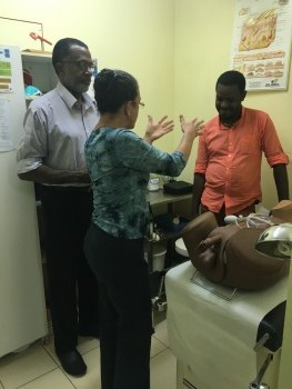 A clinician (center) practices a simulated ano-genital examination under the guidance of a clinical mentor (left).
